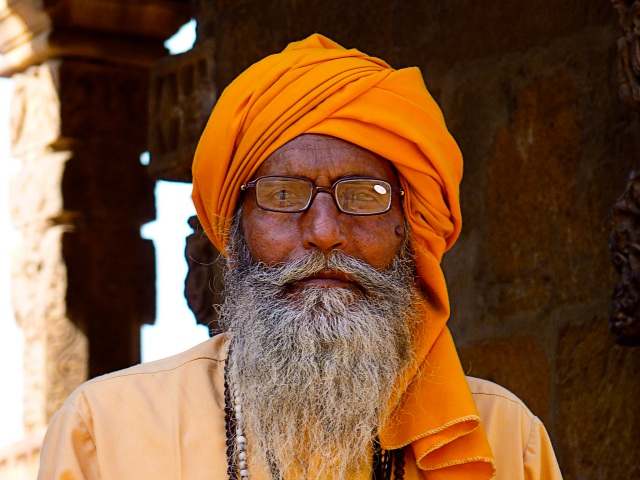 Dignified old man sheltering in the shade at the Qutab Minar