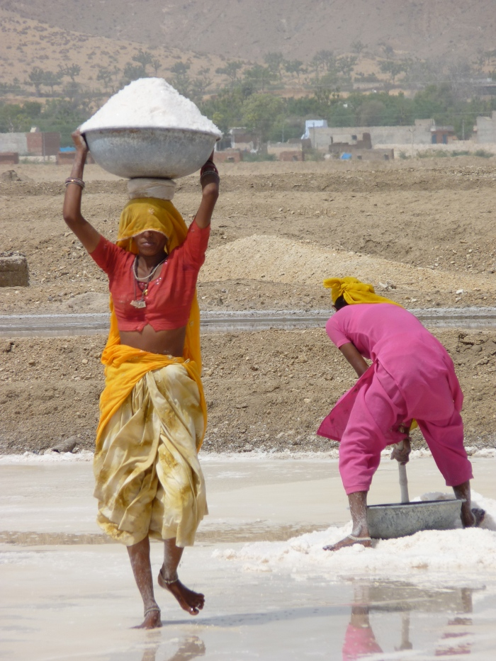 Two girls working on the desolate burning salt plains.