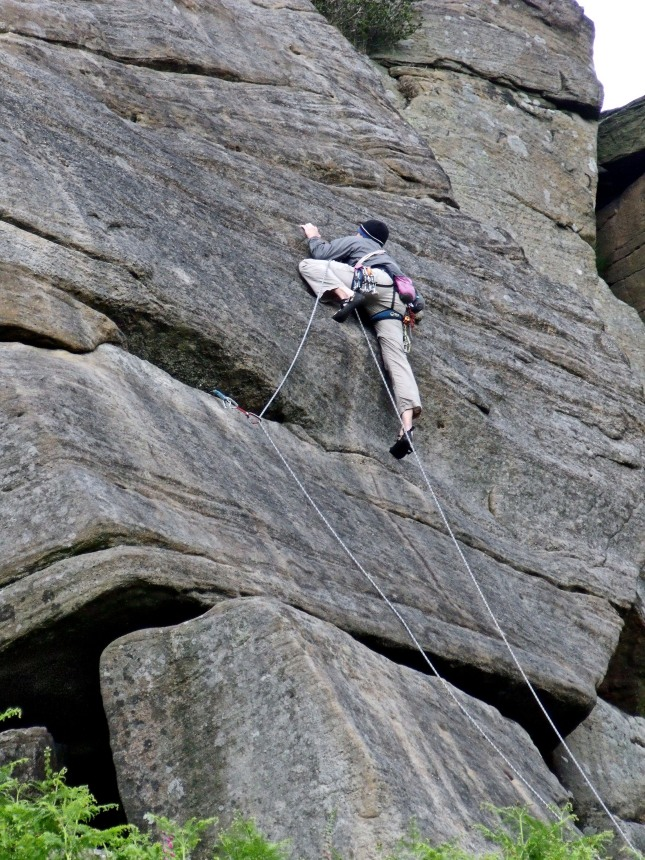 Climber on one of the world famous climbing routes on Stanage.