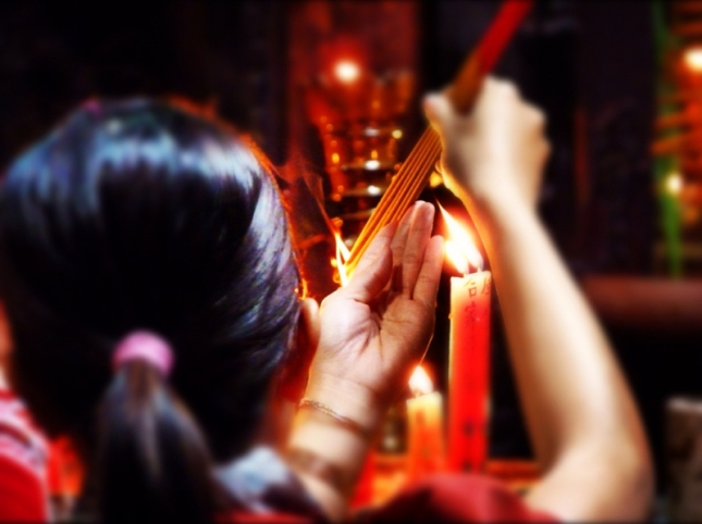Lighting joss-sticks in the temple