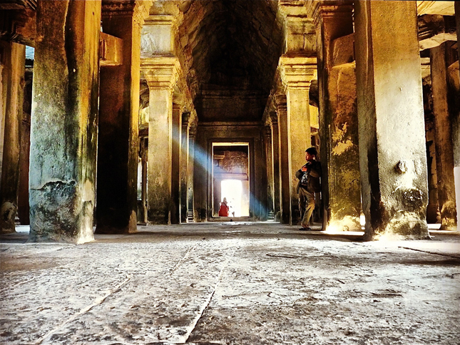 Young vagabond stands in the Temple of Angkor Wat, Cambodia